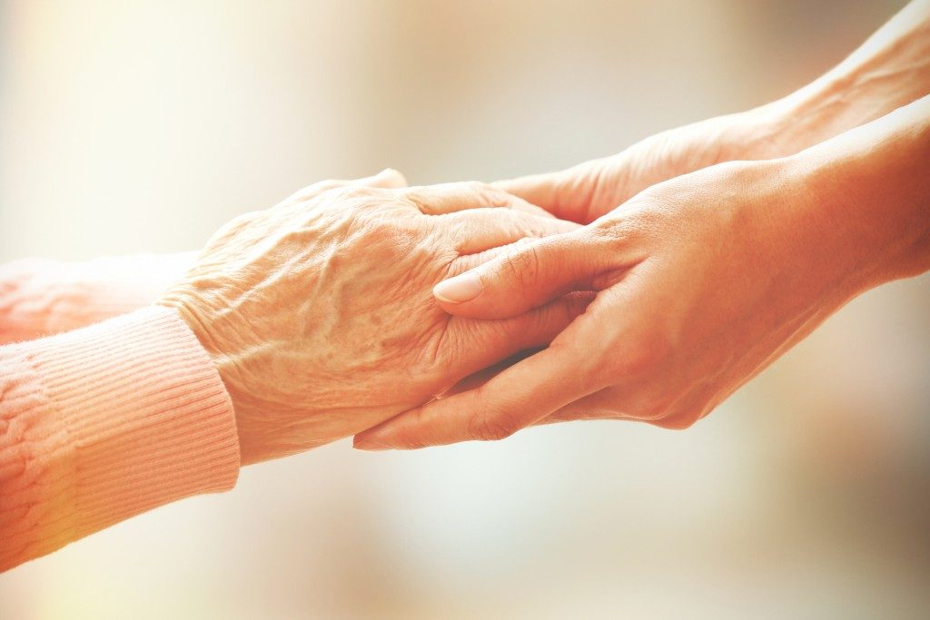 a hand of an elderly. holding another hand