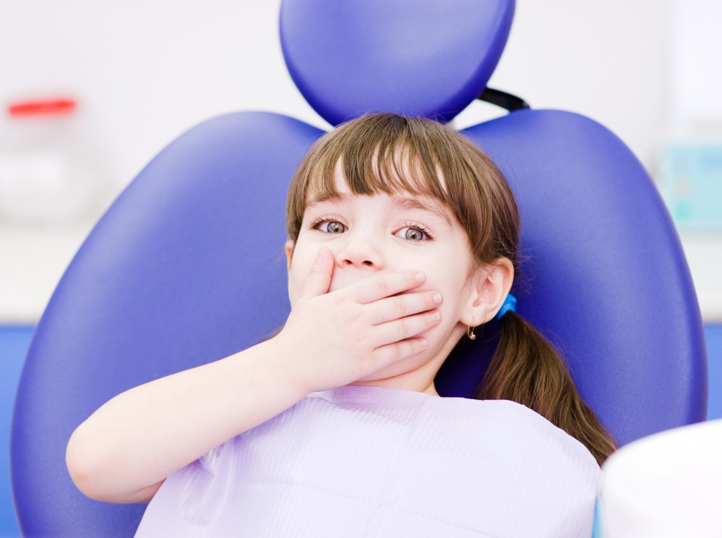 Frightened kid at dentist chair