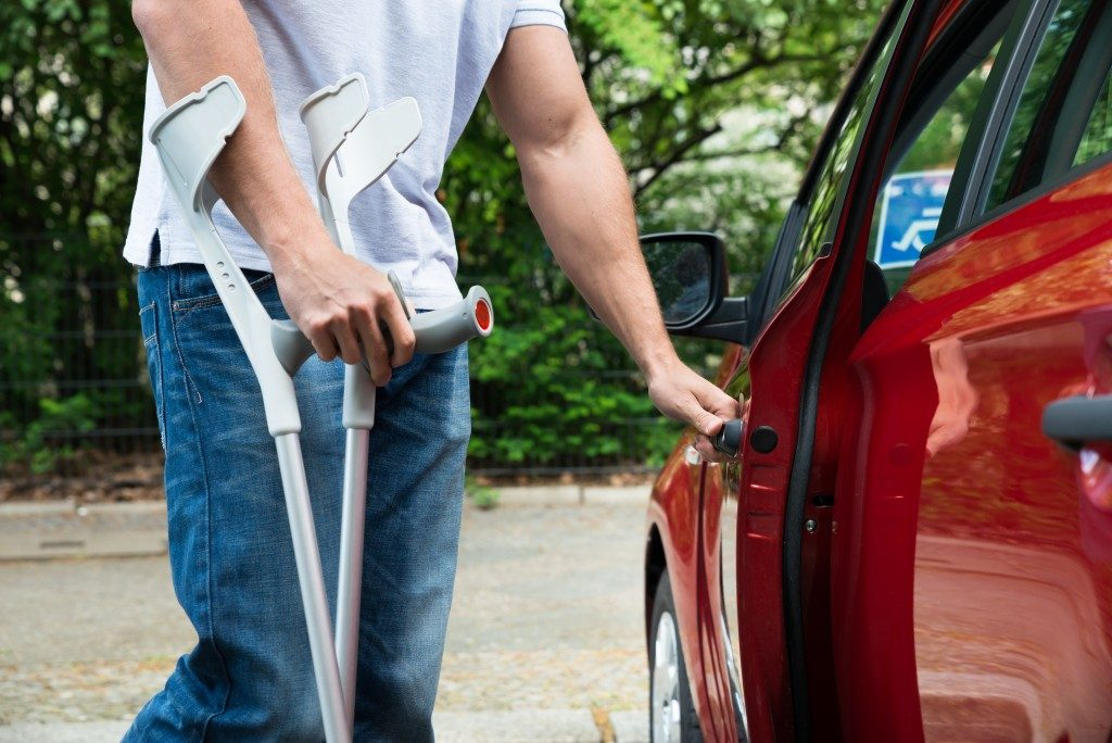 Man on crutches opening a car door