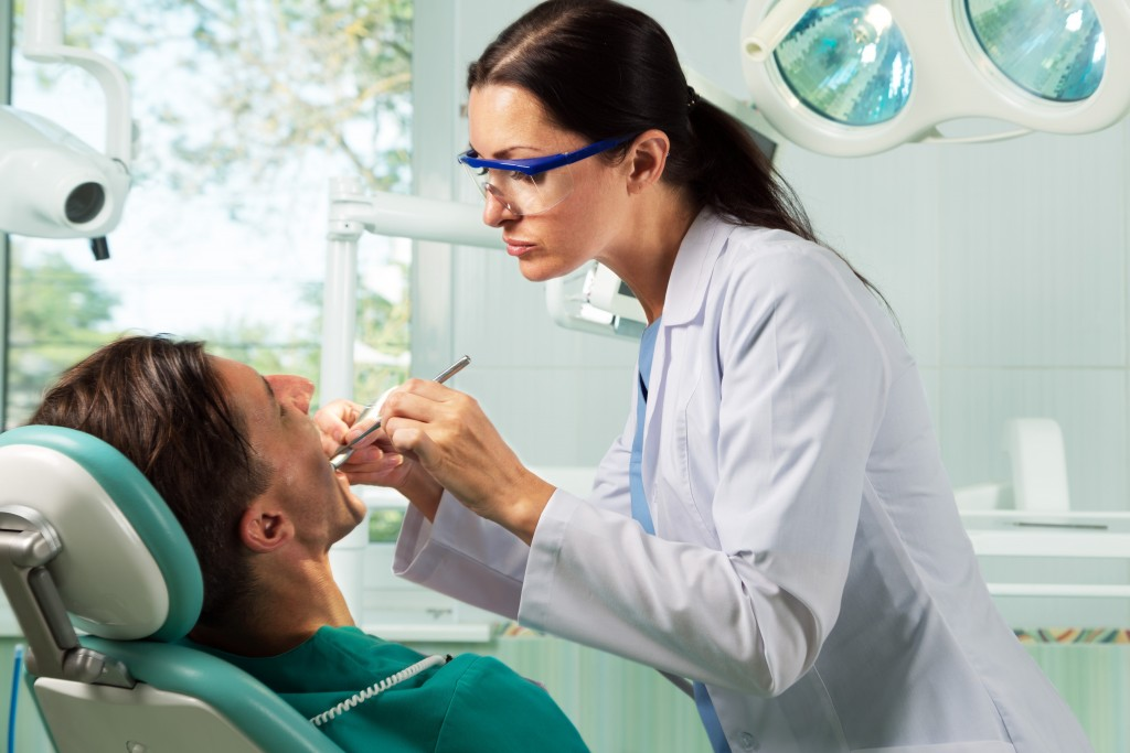 Dentist checking client's teeth