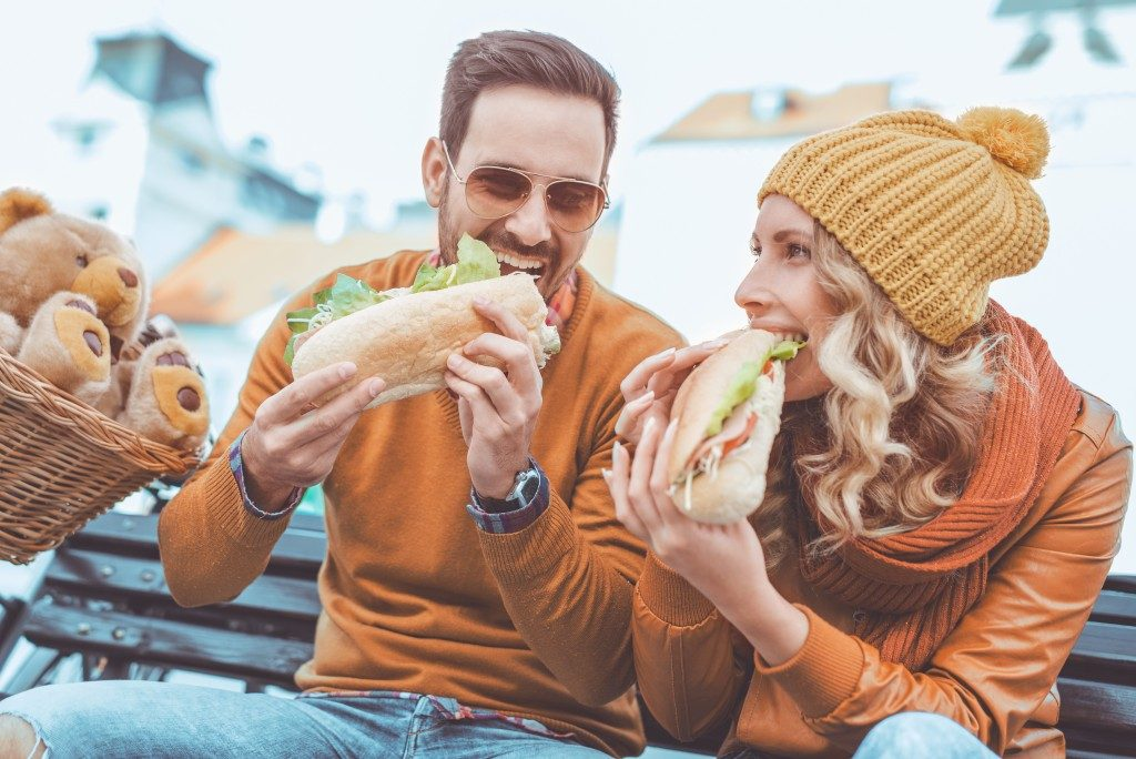 young people enjoying their large sandwich