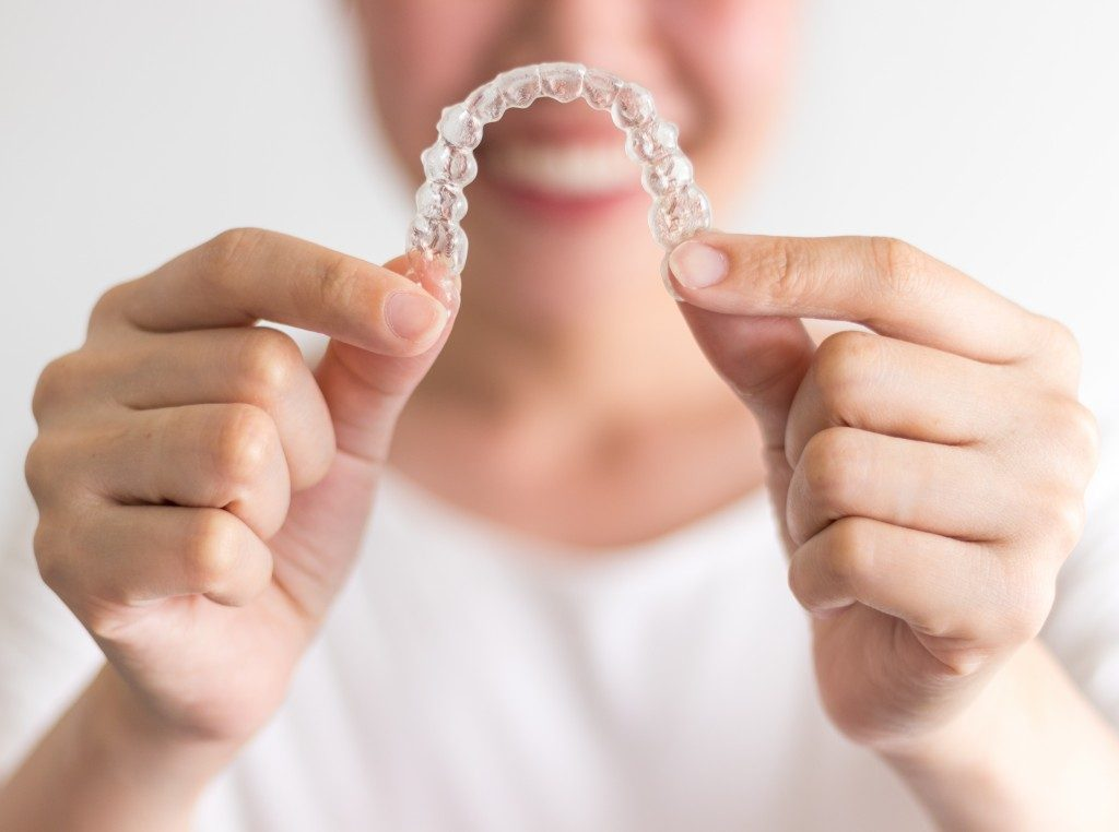 Woman holding her invisible braces