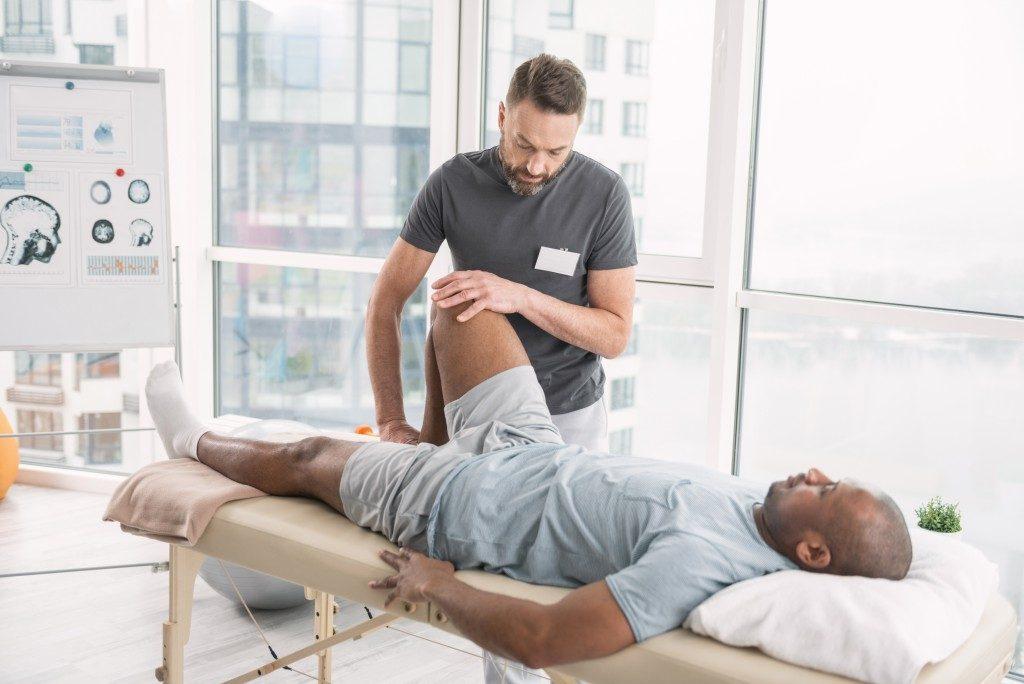 Male therapist rehabilitating a man