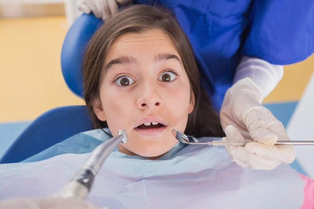 Dentist and his dental assistant examining a terrified young patient in dental clinic