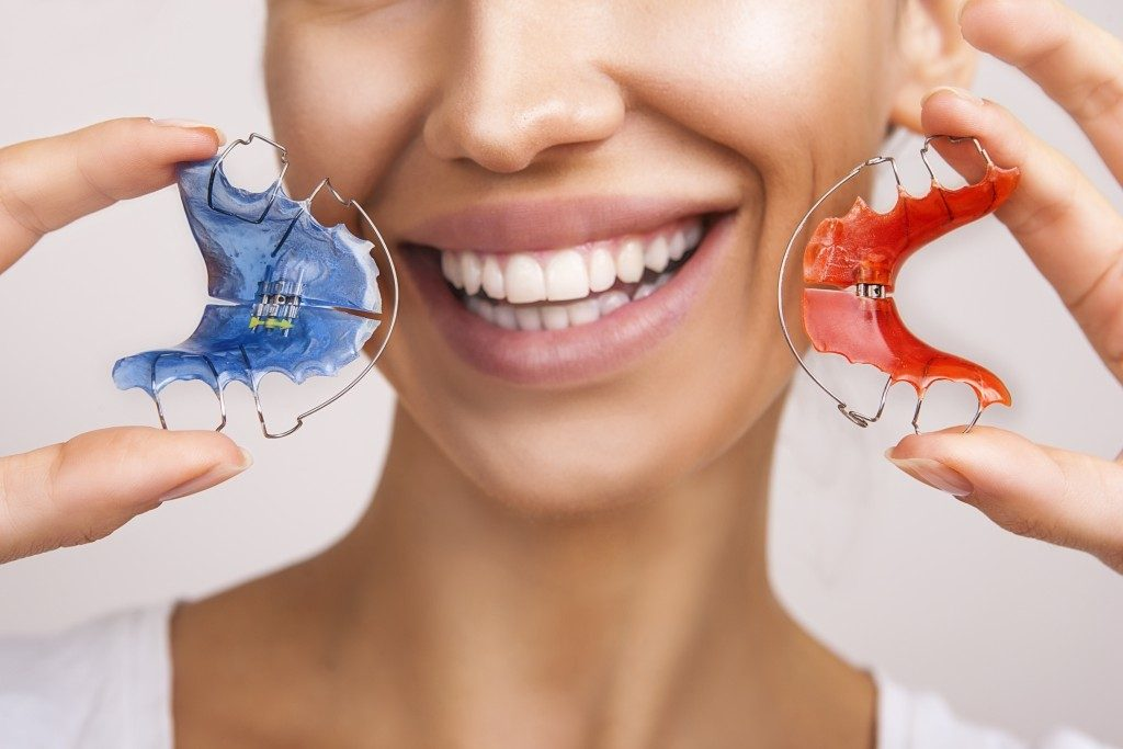 Woman holding retainer braces