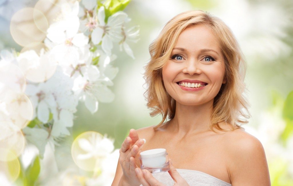 Woman holding a cream with flower background