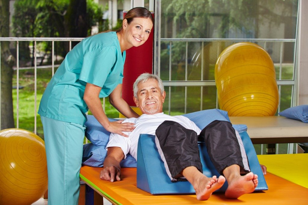 Physiotherapist assisting an elderly man
