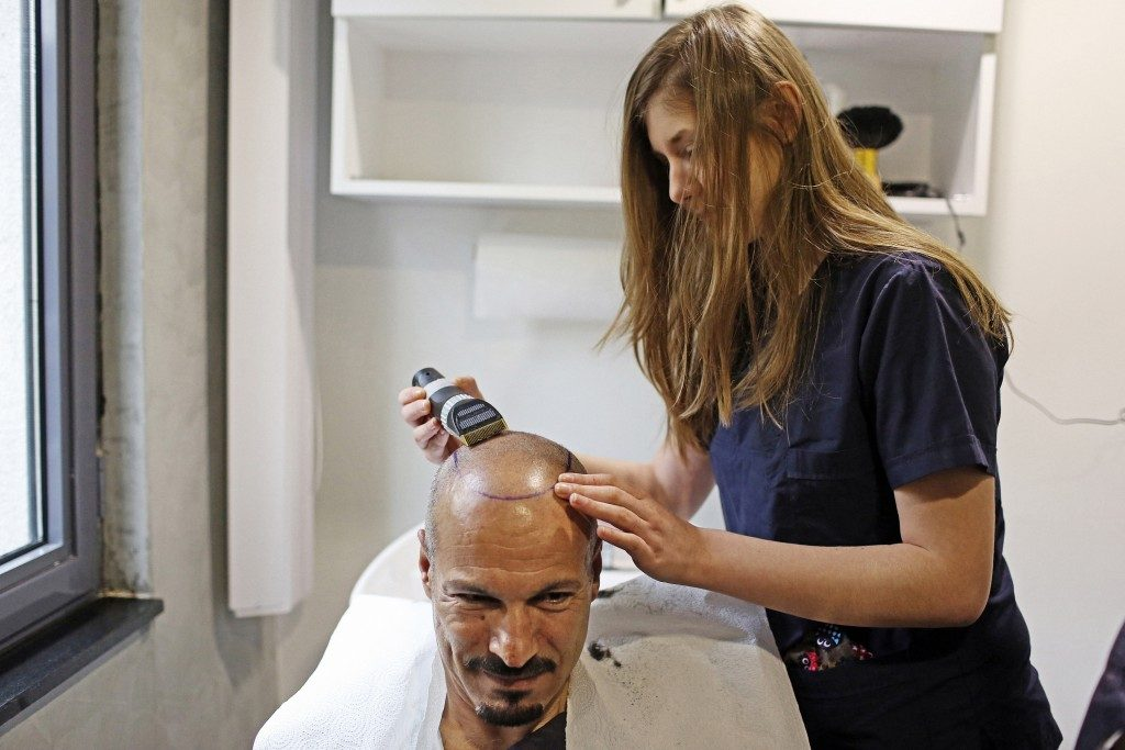 woman shaving head of man