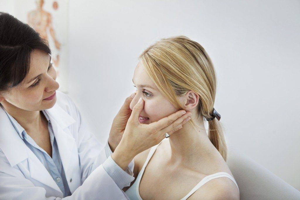 Doctor checking patient's nose for surgery
