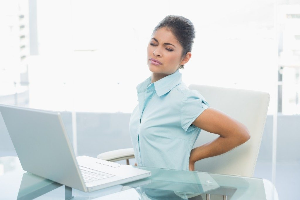 Woman having back pains while working