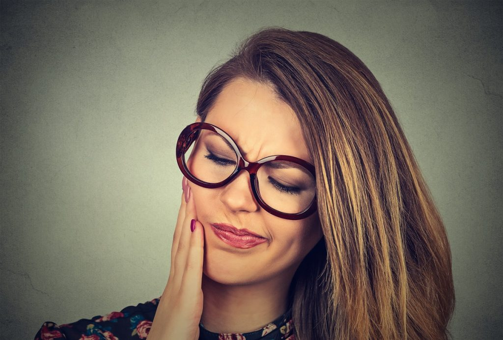 woman in glasses having pain from gum disease