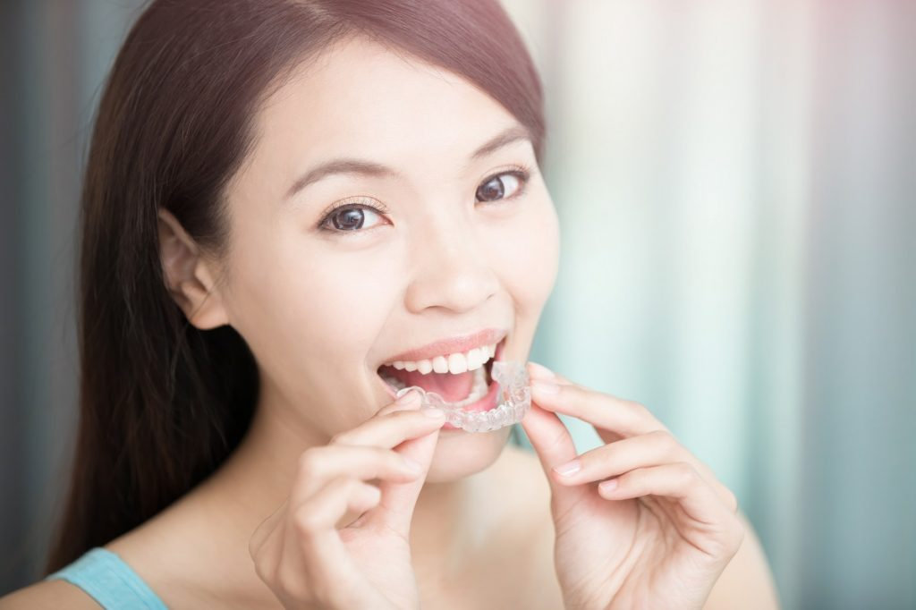 woman putting on clear braces