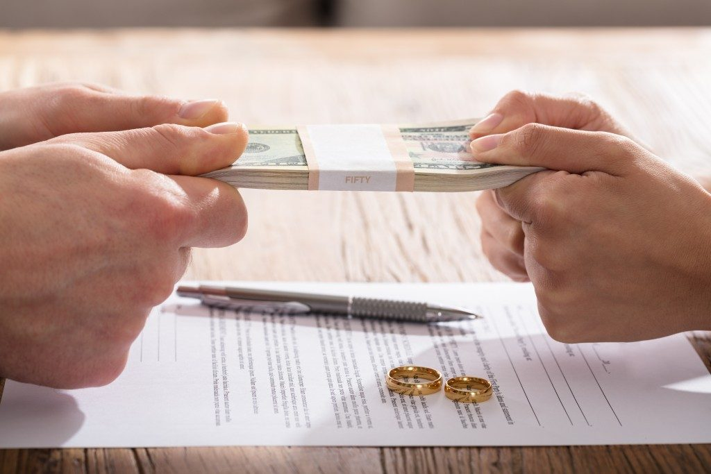 Man and woman arguing about money on top of divorce papers