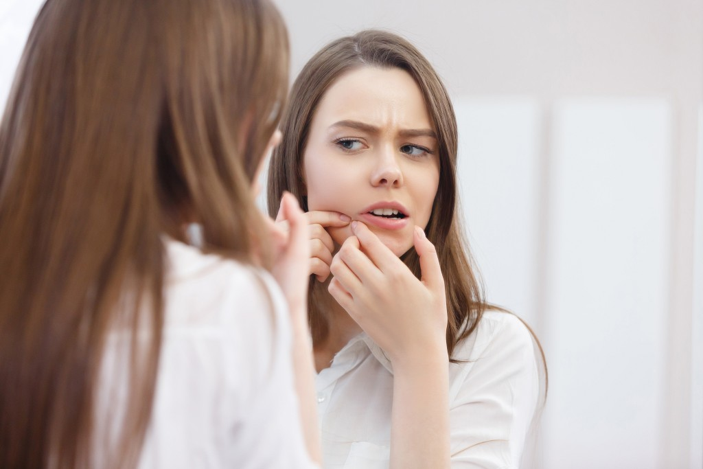 woman popping a pimple