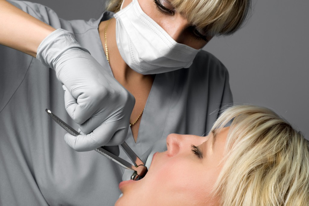 Dentist extracting female's tooth