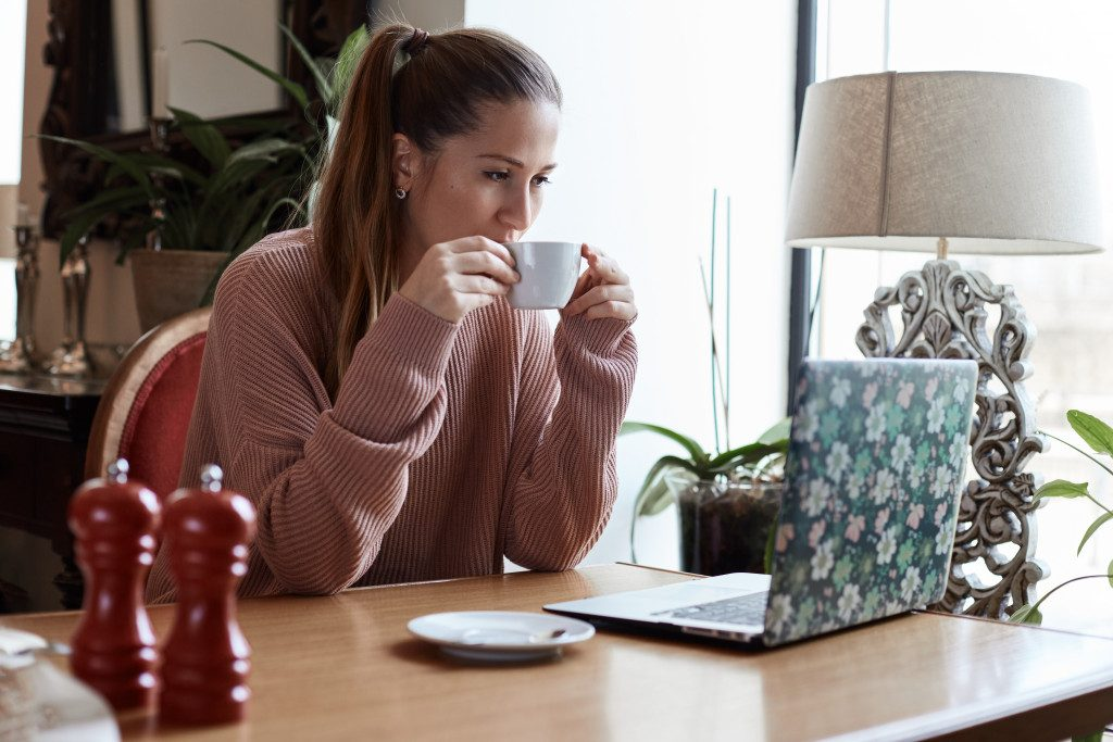 woman having a coffee while watching on her laptop